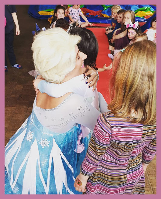 The Snow Queen recieving hug from child at party